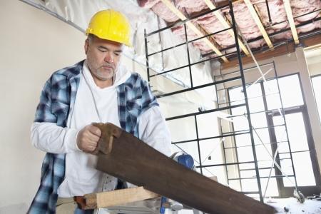 serrucho: Trabajador de la construcci�n masculina de madera de corte serio con sierra de mano
