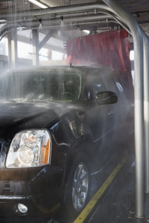 car factory: Spraying water on automobile in car wash