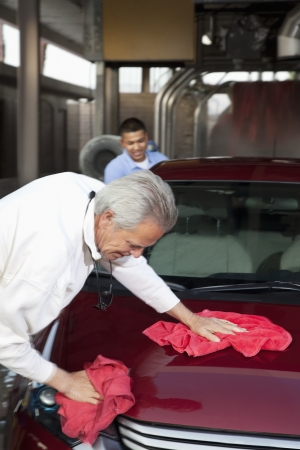 autolavaggio: proprietario maturo e giovane impiegato asciugandosi veicolo con un panno in autolavaggio