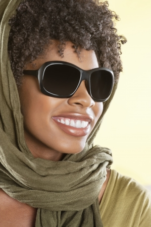 stole: Happy African American wearing sunglasses with stole over her head