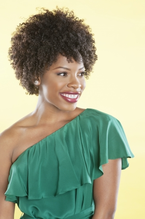 off the shoulder: Beautiful African American in an off shoulder dress looking away over colored background