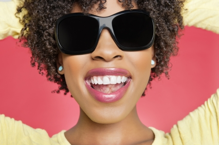 peo: Close-up of a cheerful African American woman wearing sunglasses over colored background