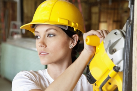 female construction worker: Female construction worker cutting wood with a power saw while looking away LANG_EVOIMAGES