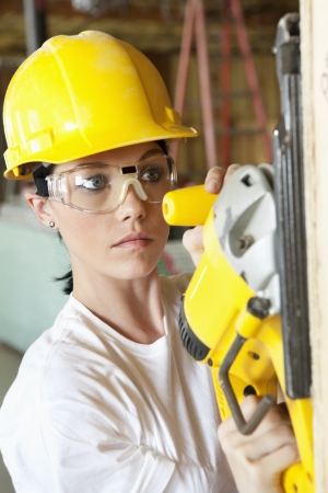 female construction worker: Serious female construction worker cutting wood with a power saw