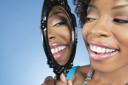 african ethnicity: Close-up of a young woman looking at herself in mirror and smiling over colored background LANG_EVOIMAGES