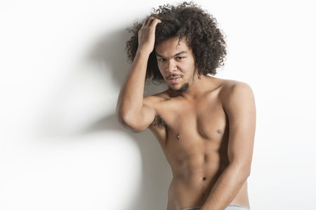 partially nude: Portrait of young man with posing with hand in hair over white background LANG_EVOIMAGES