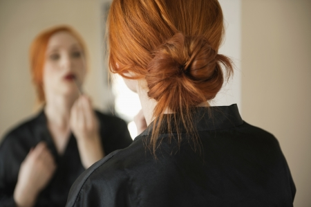 hair tied back: Back view of young woman applying makeup