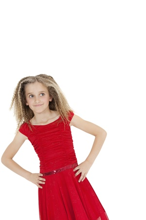 looking sideways: Tilt image of girl wearing red frock looking sideways with hands on hips over white background