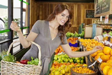 decisionmaking: Portrait of a happy young female shopping for fruits in market LANG_EVOIMAGES