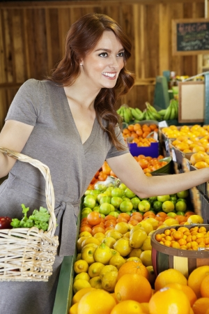 decisionmaking: Happy young woman shopping in supermarket for fruits