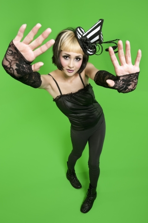 fingerless gloves: Portrait of young woman posing with fingerless gloves and headdress over green background