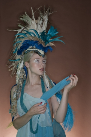 headgear: Beautiful young woman wearing costume with feather headgear over colored background