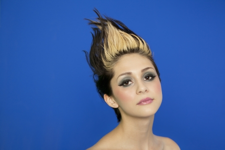 spiked hair: Portrait of beautiful young woman with spiked hair posing over blue background