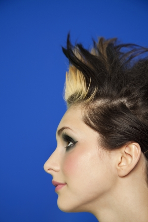spiked hair: Side view of young woman with spiked hair over colored background