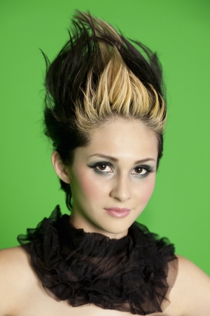 spiked hair: Portrait of beautiful young woman wearing scarf with spiked hair over green background