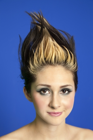 spiked hair: Portrait of a beautiful young woman with spiked hair over colored background LANG_EVOIMAGES