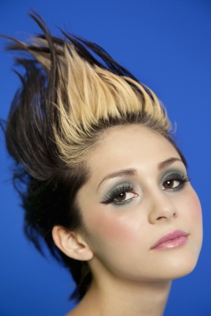 spiked hair: Close-up portrait of beautiful young woman with spiked hair over blue background