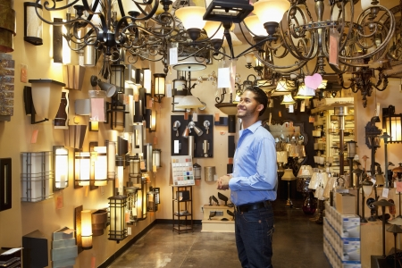 decisionmaking: Happy young man browsing for lights fixture in store
