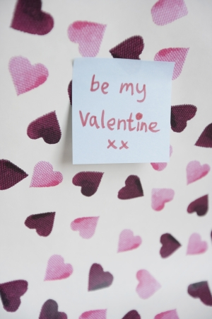 orthographic: Close-up of sticky note with a orthographic message over heart shaped background