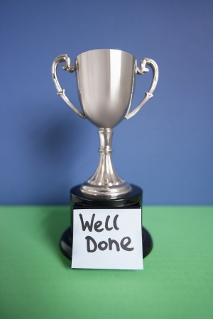 overcoming adversity: Winning trophy award with sticky note over colored background