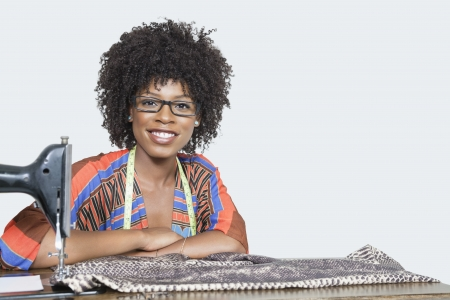 fashion industry: Portrait of an African American female fashion designer with sewing machine and cloth over gray background