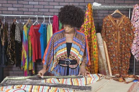 african business: African American female designer measuring cloth at design studio
