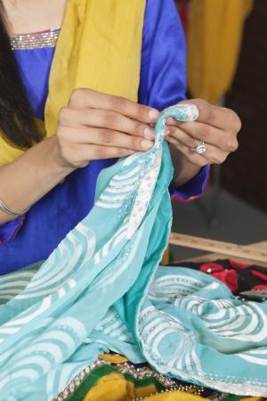 occ: Midsection of dressmaker working on a sari LANG_EVOIMAGES
