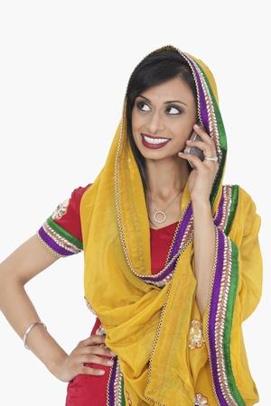 answering phone: Mujer india en desgaste tradicional respuesta de llamadas de tel�fono sobre el fondo blanco LANG_EVOIMAGES