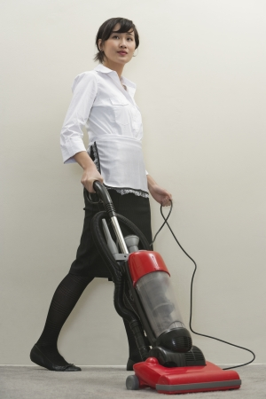 domestic staff: Full length of young female housekeeper vacuuming