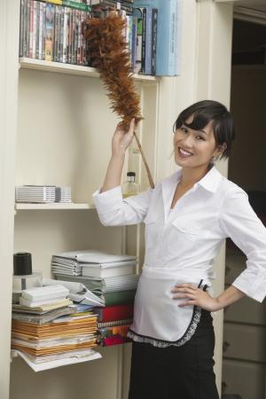 dusting: Portrait of female housekeeper dusting shelf