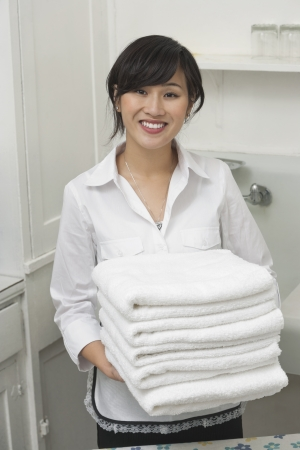 domestic staff: Portrait of young female housekeeper holding clean white folded towels