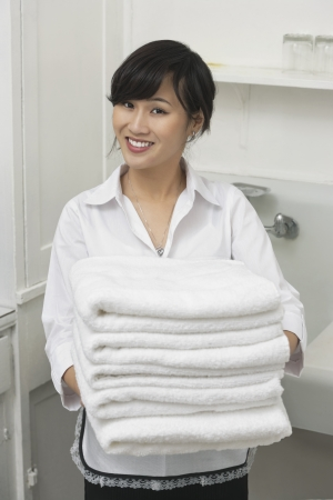 domestic staff: Portrait of beautiful housemaid holding white towels