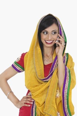 answering phone: Mujer india hermosa en la ropa tradicional de responder a la llamada de tel�fono sobre el fondo blanco LANG_EVOIMAGES