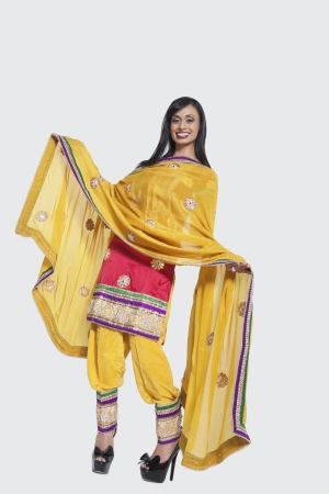 kameez: Full length of an Indian woman in salwar kameez standing over gray background