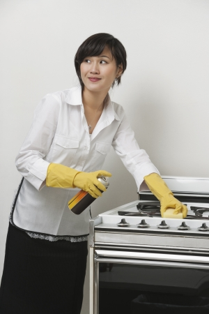domestic staff: Young maidservant looking away while cleaning stove against gray background