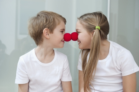 rubbing noses: Happy young siblings in white tshirts rubbing clown noses against each other