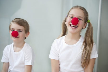 elementary age girl: Portrait of children wearing clown noses