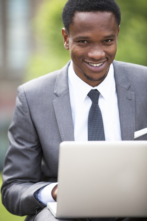 business: Close-up portrait of African American Businessman working on a laptop outdoors LANG_EVOIMAGES