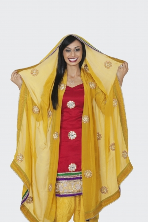 kameez: Portrait of beautiful Indian woman in salwar kameez standing over gray background
