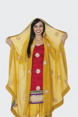 Portrait of beautiful Indian woman in salwar kameez standing over gray background