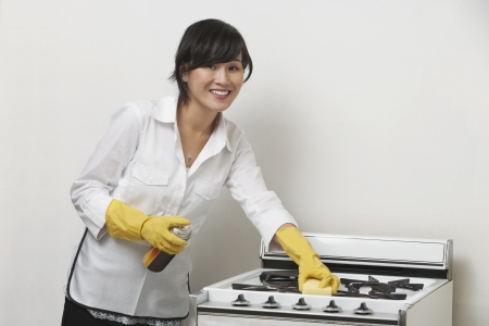 domestic staff: Portrait of young housemaid cleaning stove against gray background LANG_EVOIMAGES
