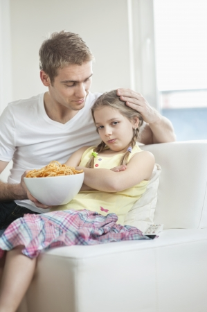 convincing: Father convincing daughter to eat wheel shape snack pellets