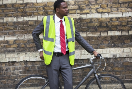 occ: Portrait of African American businessman in safety vest with Bicycle LANG_EVOIMAGES