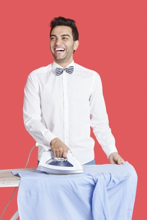 formals: Cheerful man in formals ironing shirt over red background