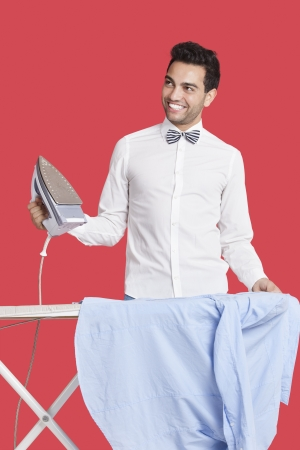 formals: Happy man in formals ironing shirt over red background