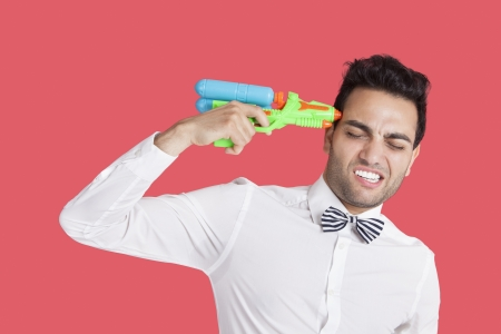 holding gun to head: Frustrated man holding toy gun to his head over red background