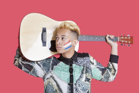 dutch flag: Teenage boy carrying guitar with Dutch flag on his face over pink background
