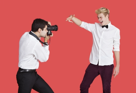 french ethnicity: Male actor being photographed by paparazzi over red background LANG_EVOIMAGES