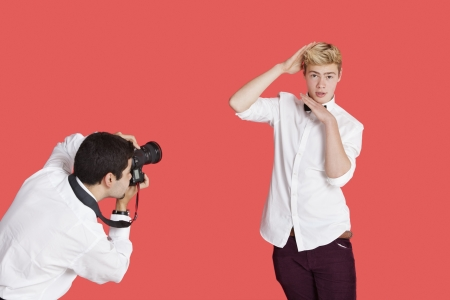 Male actor being photographed by paparazzi over red background Stock Photo