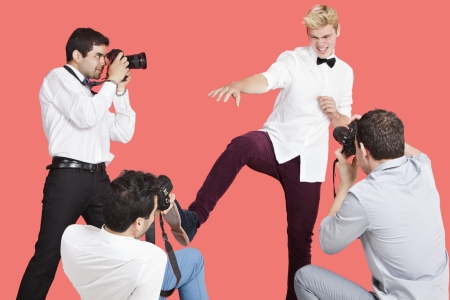 Paparazzi taking photographs of male actor over red background